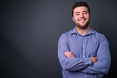 Studio shot of young businessman against gray background