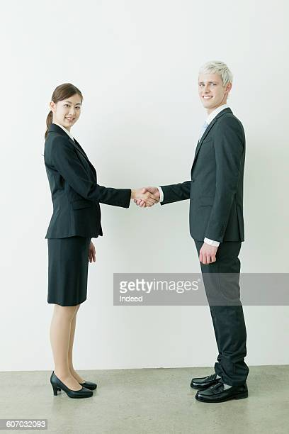 Portrait of young businessman and woman shaking hands