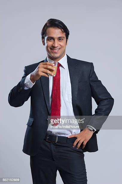 Portrait of young businessman drinking tea over gray background