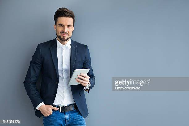 Portrait of young businessman holding digital tablet, looking confident.
