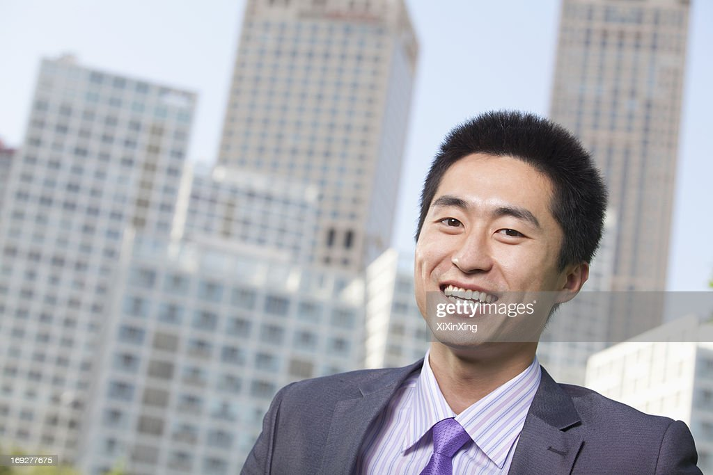 Portrait of young businessman outside in the business district, Beijing : Stock Photo