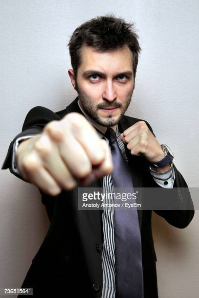 Portrait Of Young Businessman Punching Against Wall