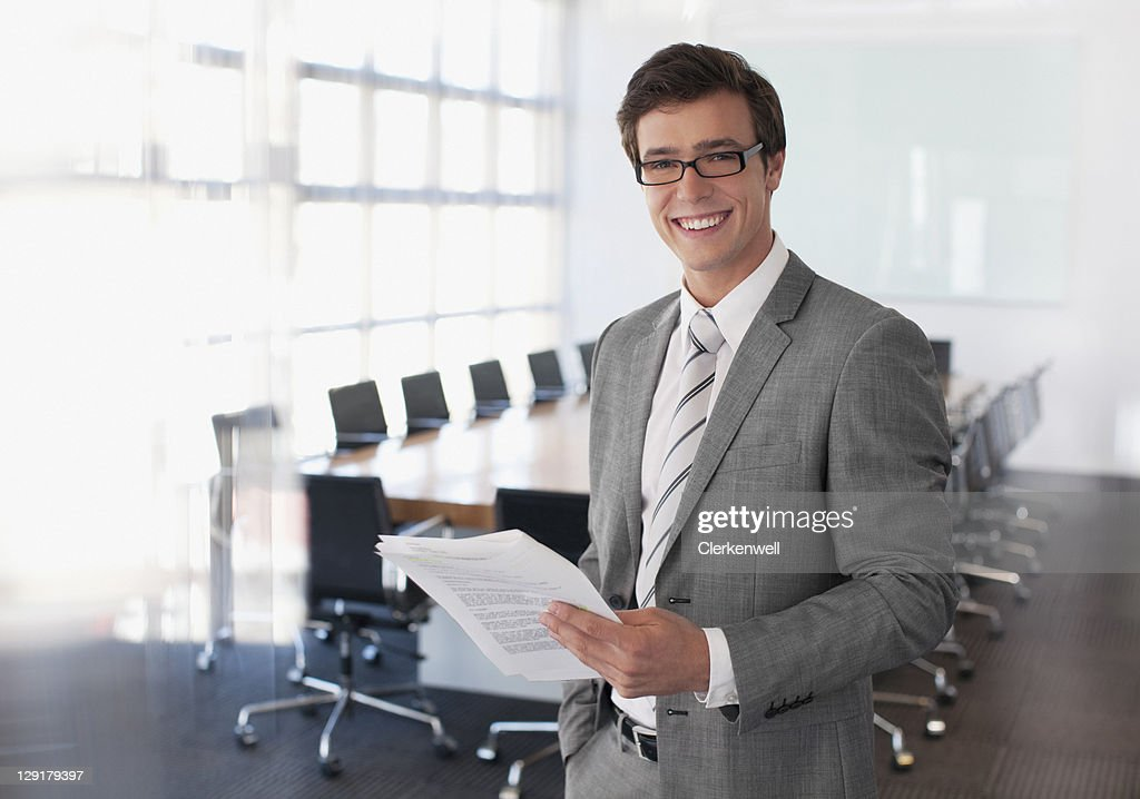 Portrait of young businessman reading documents in board room : Stock Photo