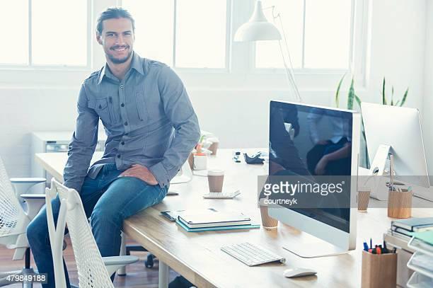 Porträt des jungen Geschäftsmann, sitzen an einem Schreibtisch.