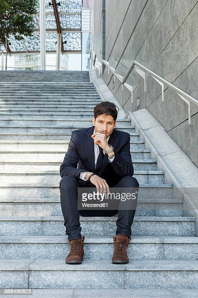 Portrait of young businessman sitting on stairs