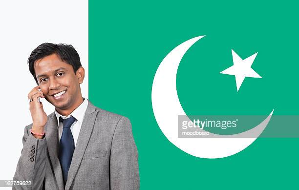 Portrait of young businessman using cell phone over Pakistani flag