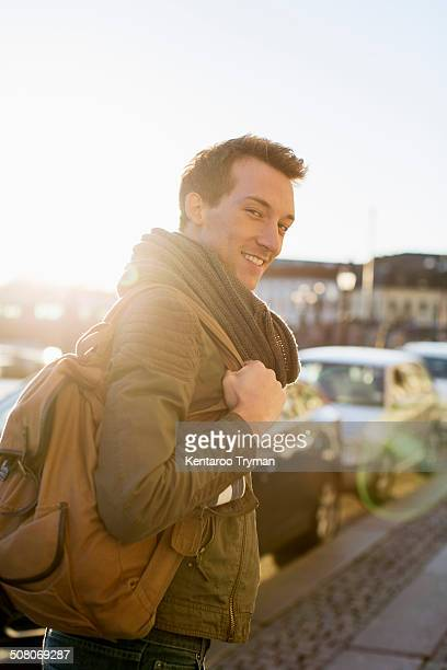 Portrait of young businessman with backpack walking on footpath