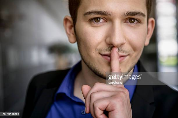 Portrait of young businessman with finger on lips in office