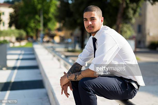 Portrait of young businessman with tatoos on his forearms sitting on railing