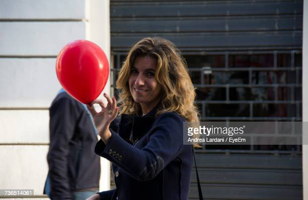 Portrait Of Young Businesswoman Holding Red Balloon At Outdoors