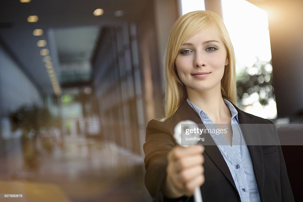 Portrait of young businesswoman holding up network power cable in office