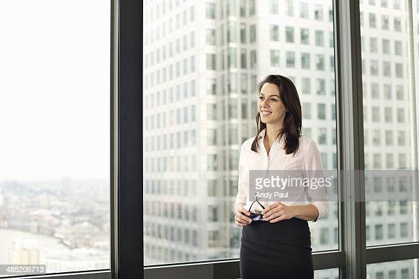 Portrait of young businesswoman looking out of office window