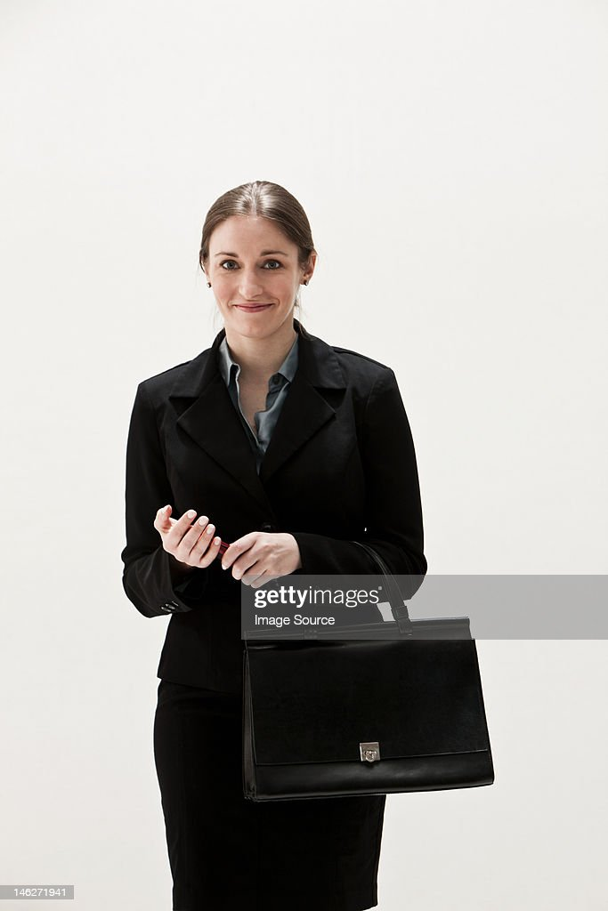 Portrait of young businesswoman smiling, studio shot : Stock Photo