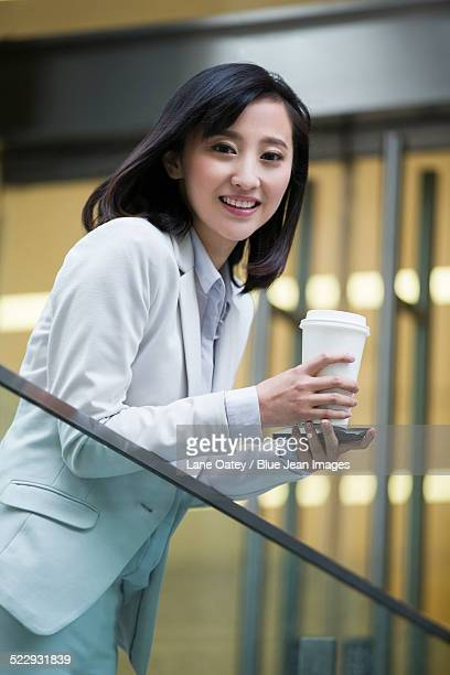 Portrait of young businesswoman with coffee cup