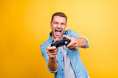 Portrait of young, cheerful, attractive, very excited guy holding joystick and playing video games over yellow background