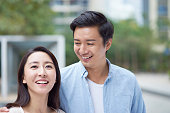 portrait of young Chinese couple standing & smiling outdoor