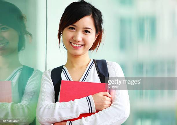 portrait of young college student holding book