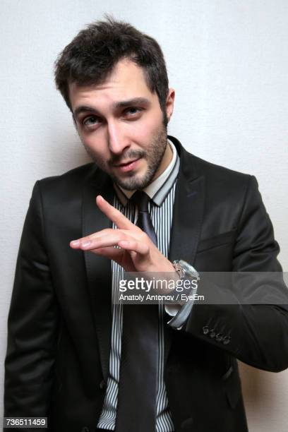Portrait Of Young Confident Businessman Against Wall