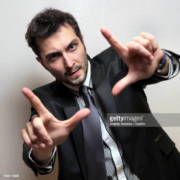 Portrait Of Young Confident Businessman Gesturing Against Wall