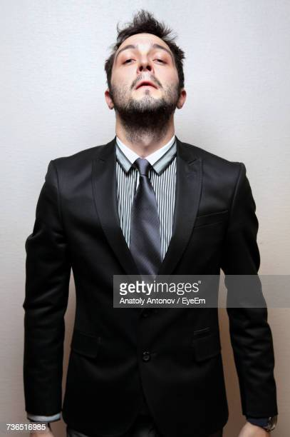 Portrait Of Young Confident Businessman Standing Against Wall
