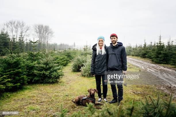 Portrait Of Young Couple And Their Dog, Outdoors Looking For The Perfect Christmas Tree