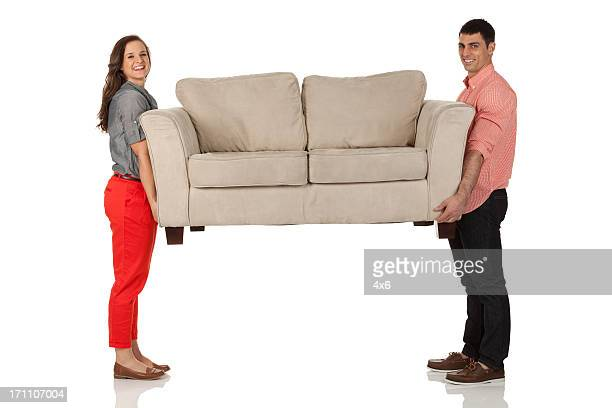 Portrait of young couple carrying a couch
