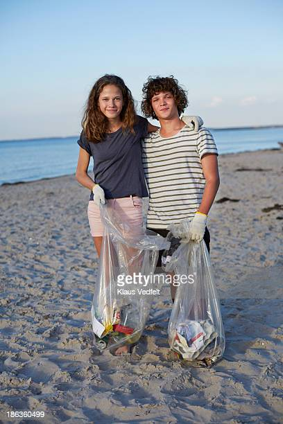 Portrait of young couple collecting trash on beach