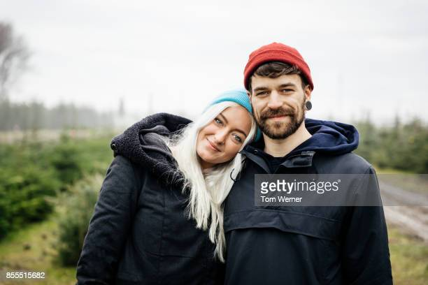 Portrait Of Young Couple Embracing Outdoors In Pine Forest