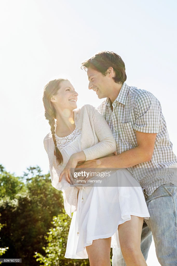 Portrait of young couple embracing outdoors : Photo