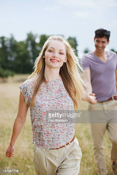 Portrait of young couple holding hands in rural field