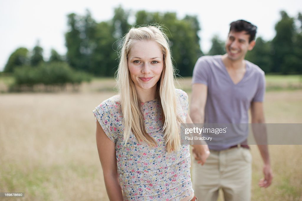 Portrait of young couple holding hands in rural field : Stock Photo