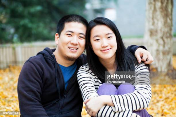 Portrait of young couple in a park with autumn leaves