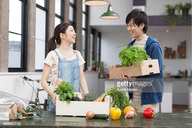 Portrait of young couple in kitchen with herbs and vegetables