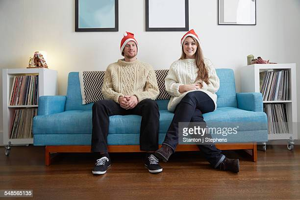 Portrait of young couple in santa hats sitting on living room sofa
