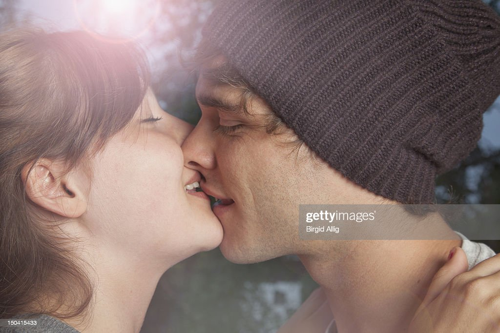 Portrait of young couple, kissing : Stock Photo