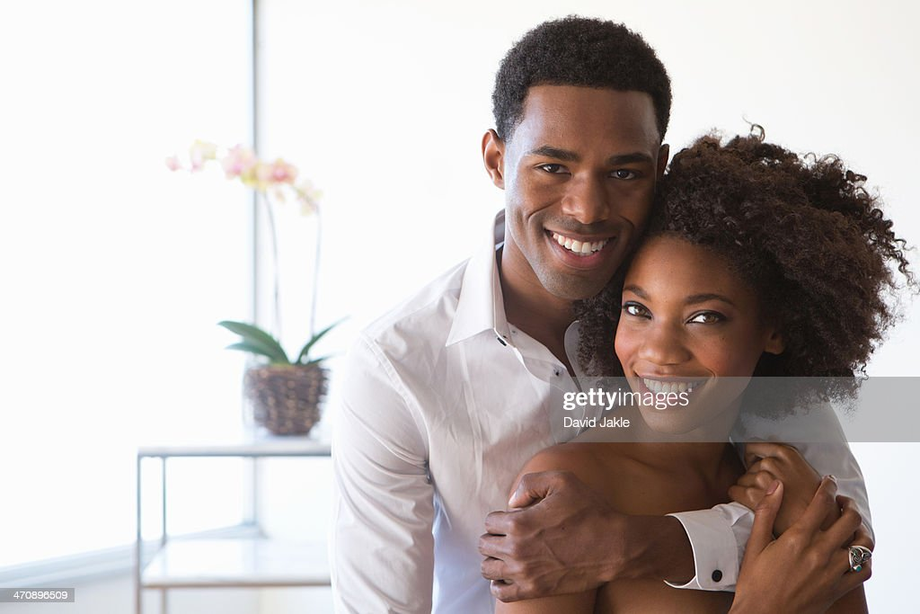 Portrait of young couple, man with arm around woman
