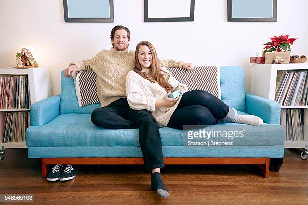 Portrait of young couple on living room sofa with christmas gift