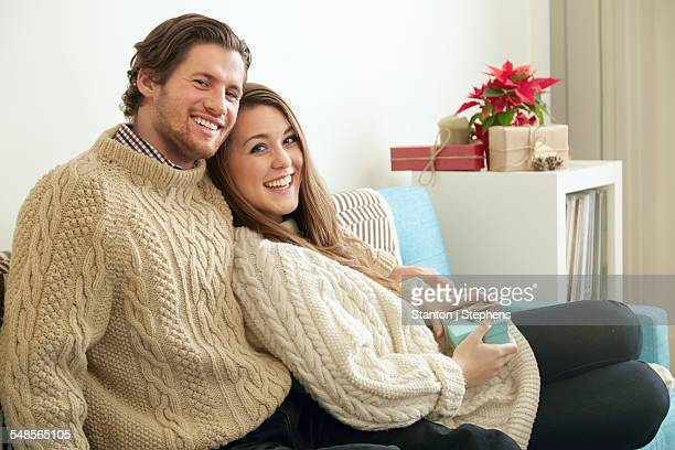 Portrait of young couple on sofa with christmas gift