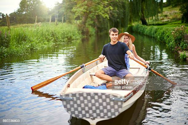 Portrait of young couple rowing on rural river