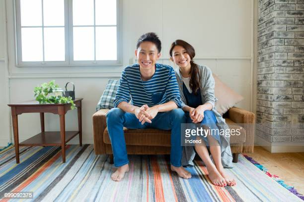 Portrait of young couple, sitting on sofa