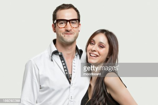 Portrait of young couple smiling together against gray background : Stock Photo