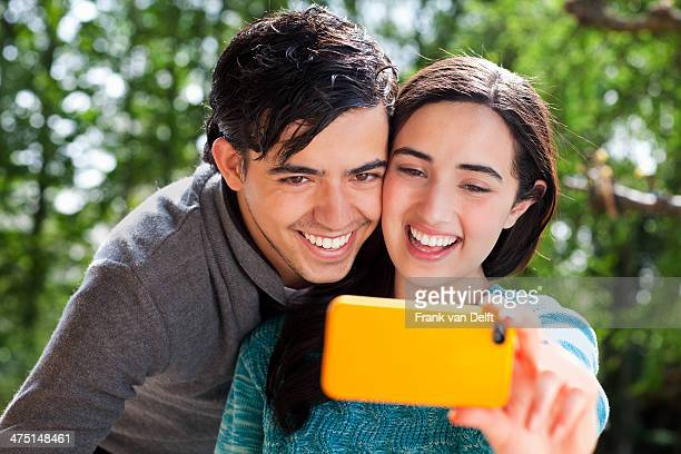 Portrait of young couple taking self portrait in garden