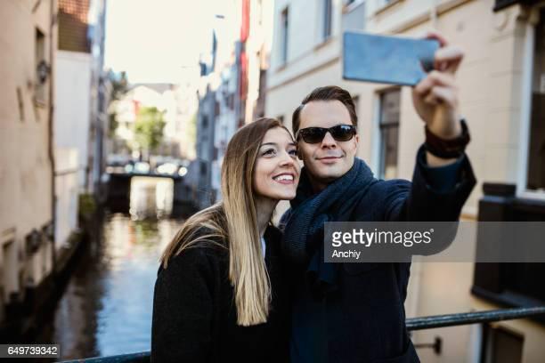 Portrait de jeune couple prenant selfie sur le pont.