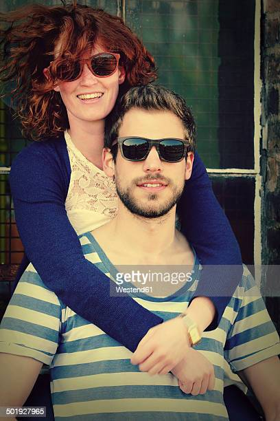 Portrait of young couple wearing sunglasses