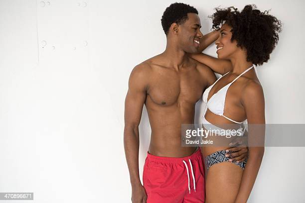 Portrait of young couple wearing swimwear against white background