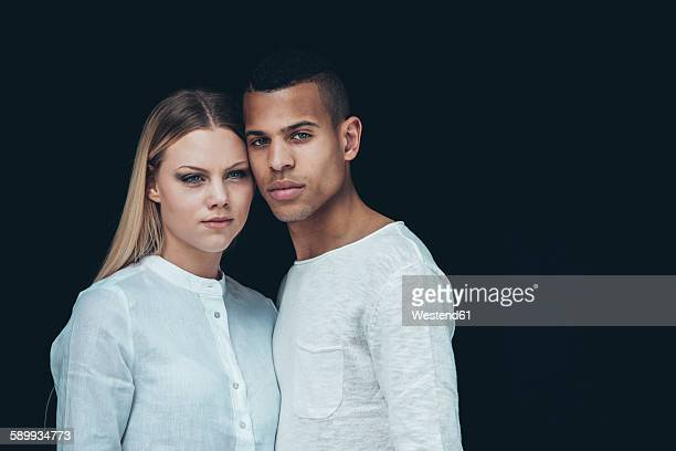 Portrait of young couple wearing white clothes head to head in front of black background
