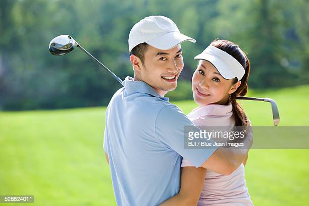 Portrait of young couple with golf clubs