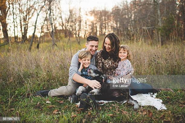 Portrait of young couple with son, daughter and dog in field