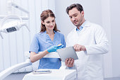 portrait of young dentists discussing work together and using tablet in dental clinic