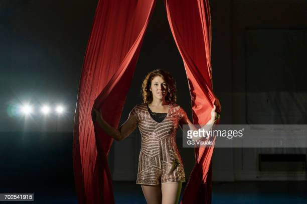 Portrait of young female acrobat entering between red curtains